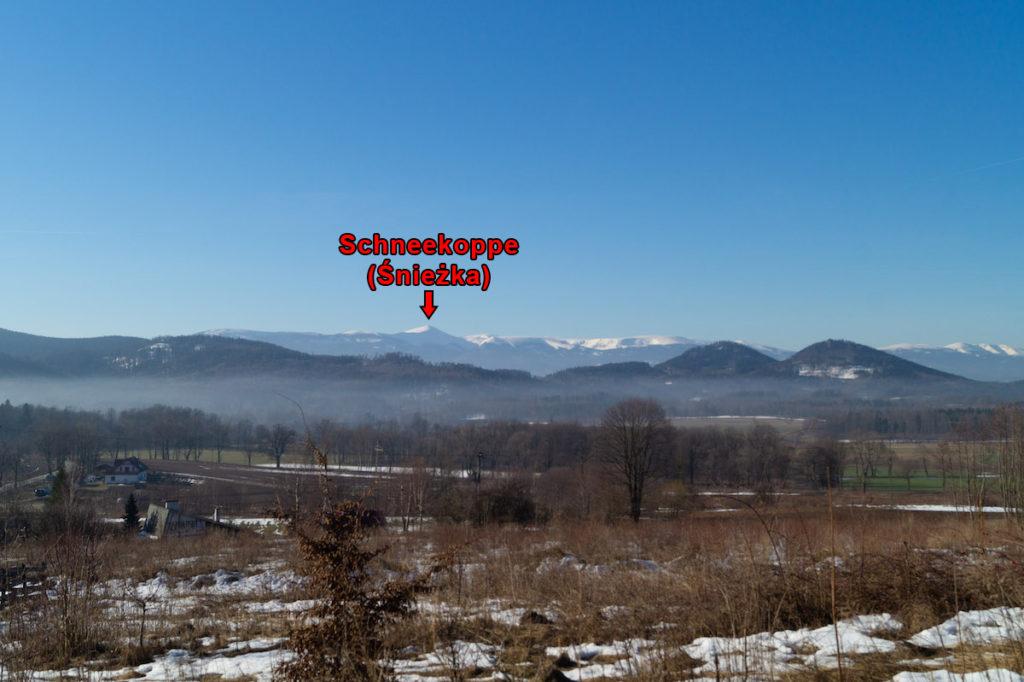 Im Vordergrund des Landshuter Kammes mit schneebedeckten Bergen im Hintergrund und in Weiss (der höchste Gipfel des Sudetenlandes)